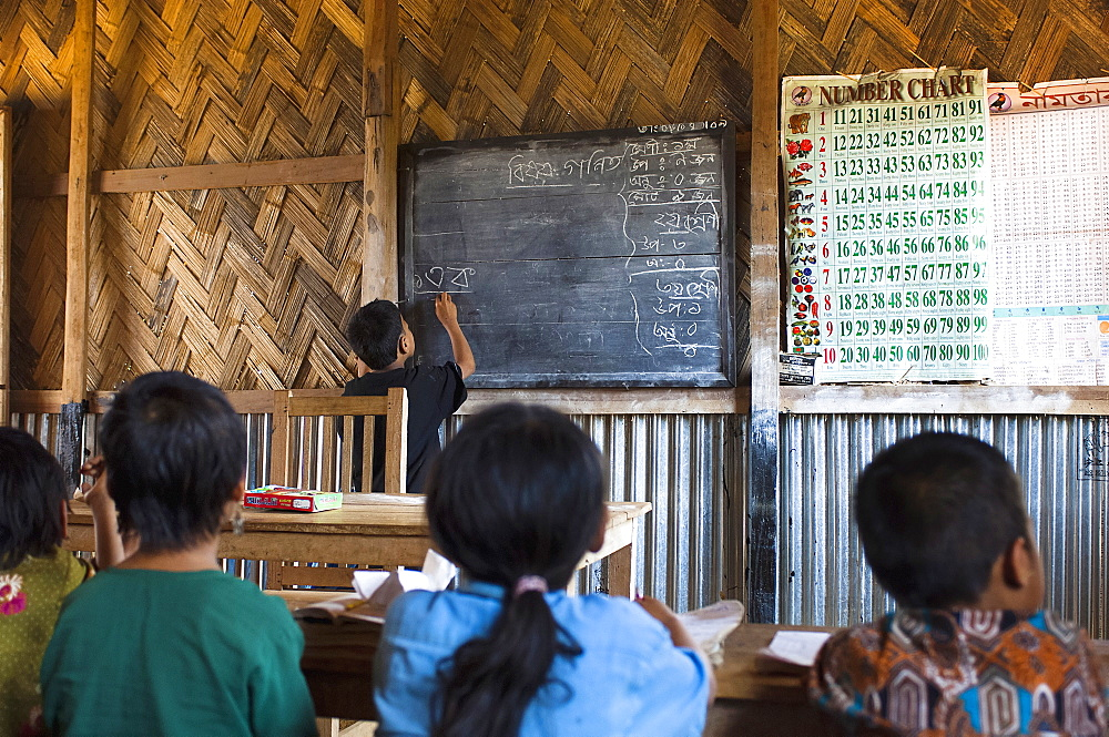 Bangladesh, Chittagong Division, Bandarban, School boy writing Bangladeshi on the blackboard in a UN supported primary school classroom.