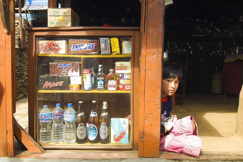 Nepal, Himalayas, Pokhara, Girl sat in a shop doorway on a trekking route with western snacks for sale.
