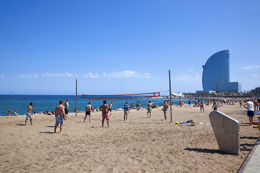 Spain, Catalonia, Barcelona, Playa de St Sebastia, Barceloneta Beach, people playing volleyball with the W hotel behind.