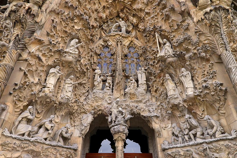 Spain, Catalunya, Barcelona, Basa­lica i Temple Expiatori de la Sagrada Fama­lia, Generally known as Sagrada Familia, The Nativity facade showing the original detailed work of Antoni Gaudi.