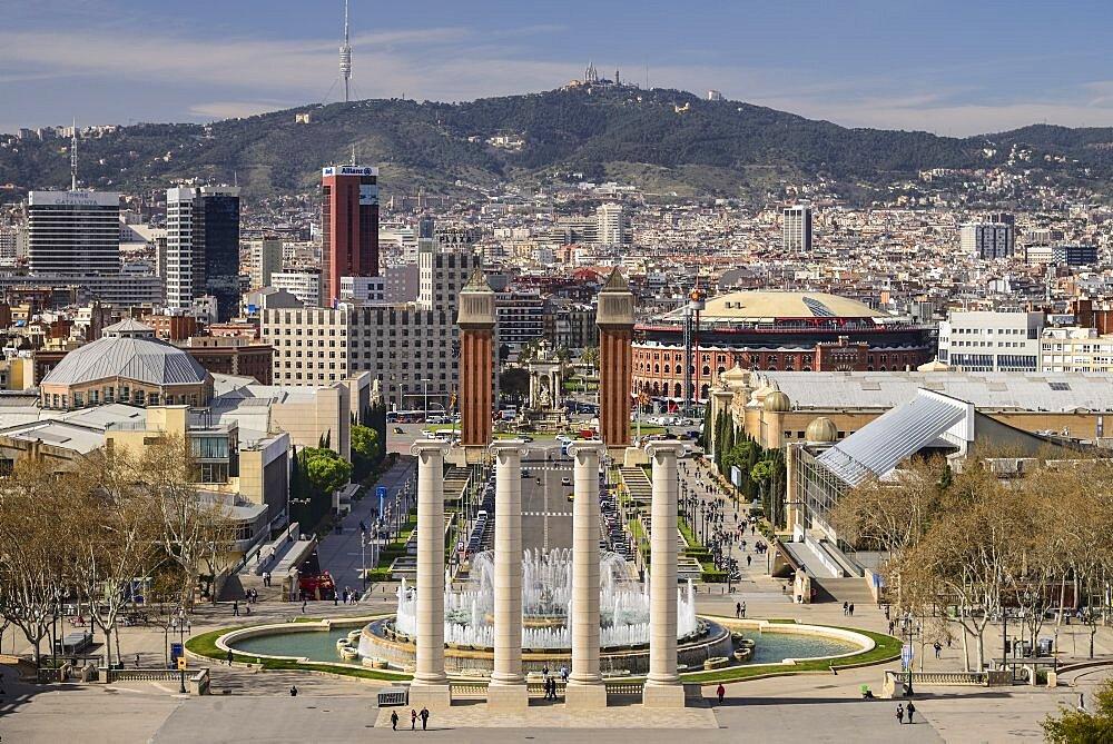 Spain, Catalunya, Barcelona, Placa d'Espanya and general vista towards Tibidabo mountain with Venetian Towers and Arenas de Barcelona bullring prominent in the central area.