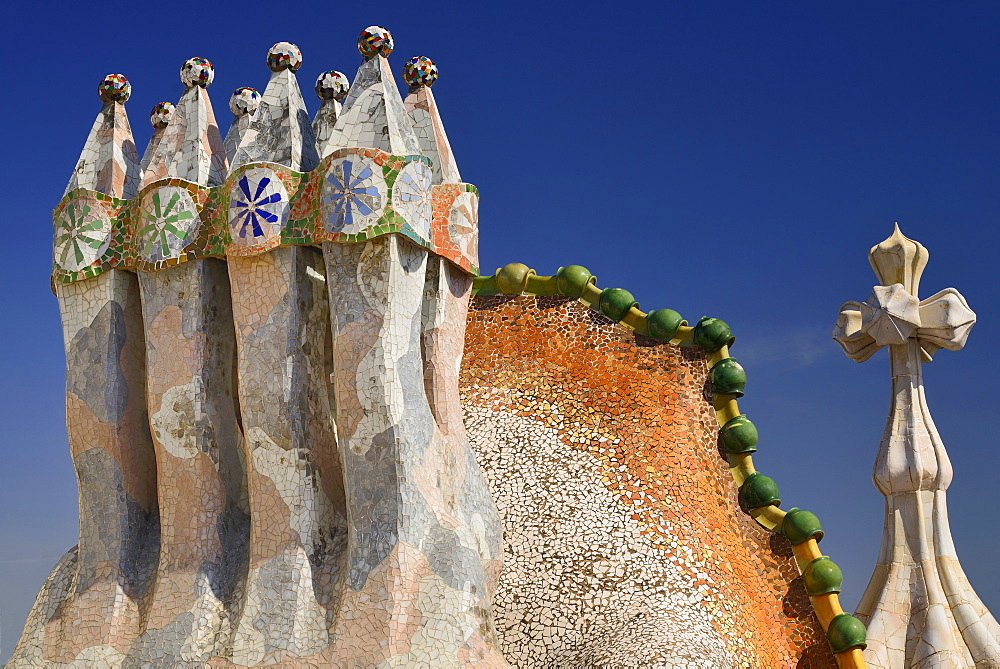 Spain, Catalunya, Barcelona, Antoni Gaudi's Casa Batllo building, colourful chimney pots on the roof terrace with the four armed cross also inclluded. - 797-12012