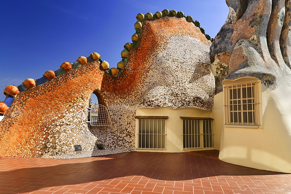 Spain, Catalunya, Barcelona, Antoni Gaudi's Casa Batllo building, detail of dragon's back tile feature on the roof terrace with windows included.