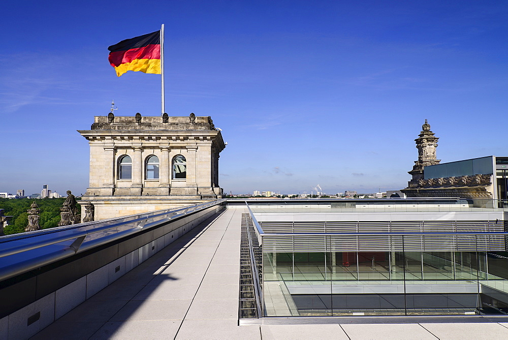 Germany, Berlin, German flag fluttering on a corner tower of the Reichstag building as seen from the rooftop terrace.