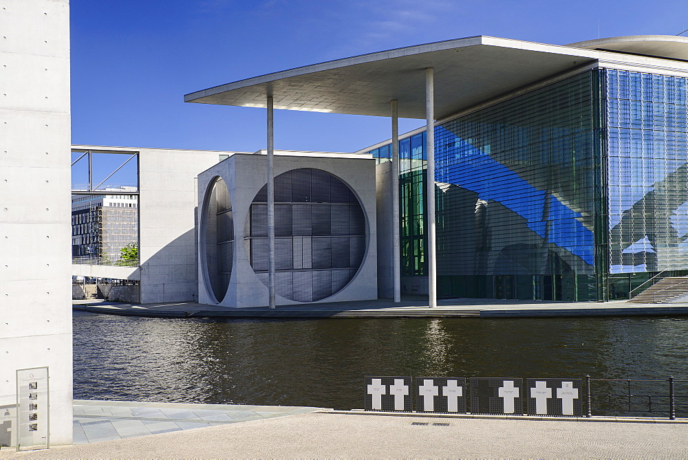 Germany, Berlin, Marie Elisabeth Luders Haus which is a service centre of the Bundestag located across the River Spree behind the Reichstag with memorial crosses to Berlin Wall victims in the foreground.