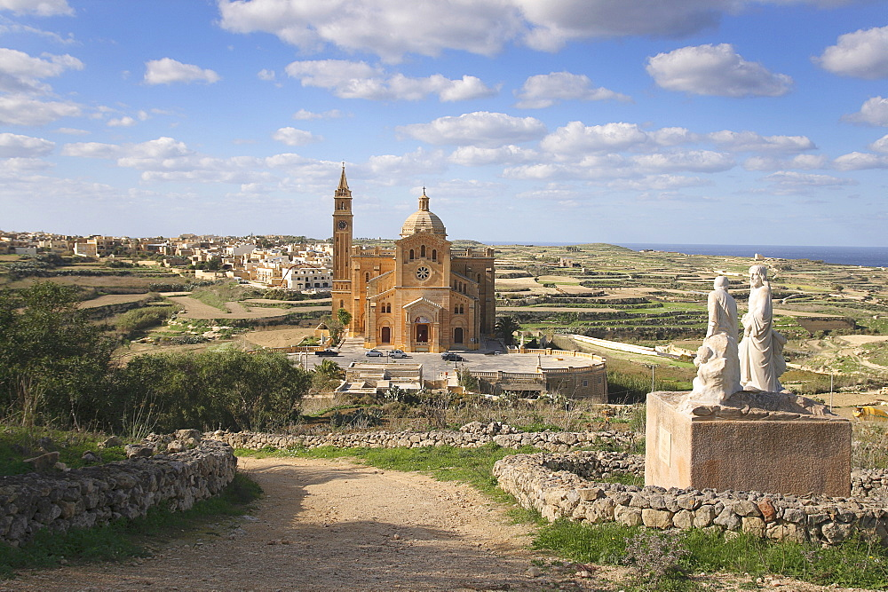 Malta, Gozo, Ta Pinu, Sanctuary church seen form hilltop with statues in the foreground.
