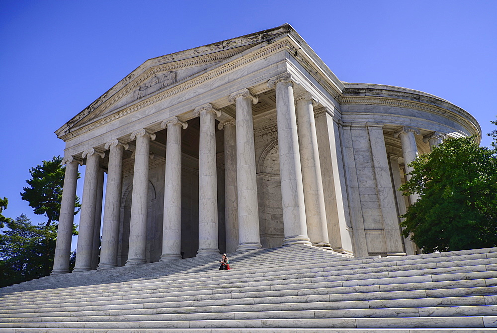 USA, Washington DC, National Mall, Thomas Jefferson Memorial, a lone tourist sitting on the steps beneath the facade.