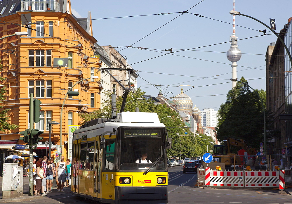 Germany, Berlin, Mitte, tram exiting Oranienburger Strasse with the Neue Synagogue and TV tower behind.