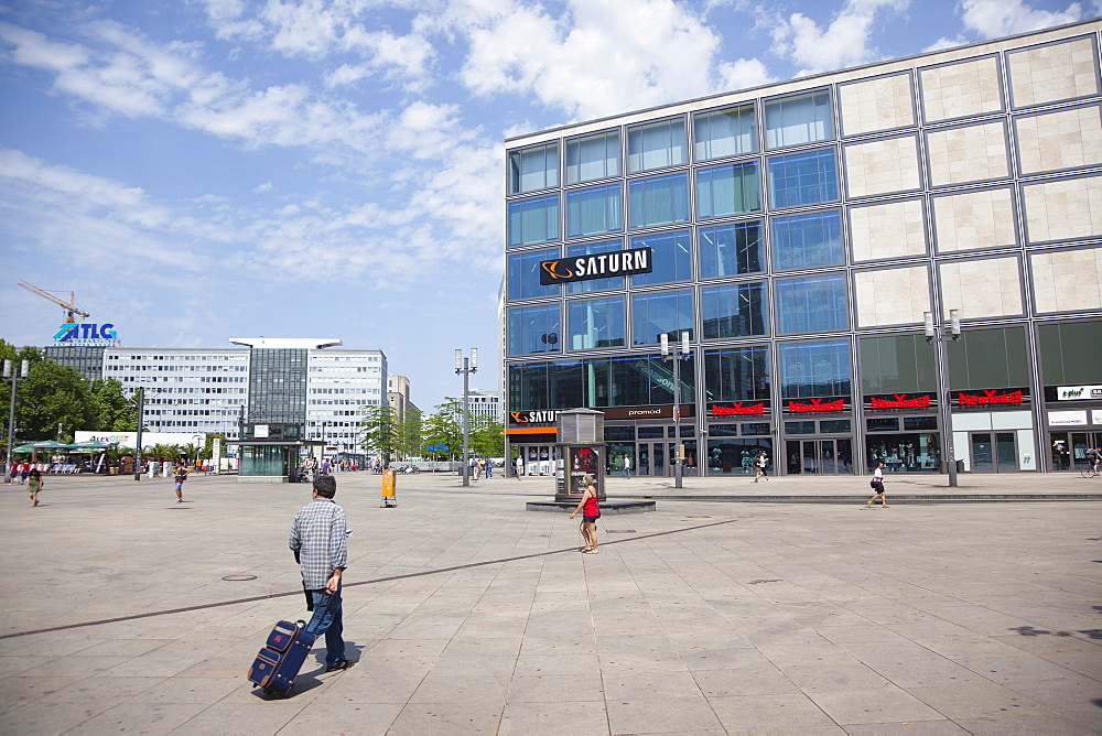 Germany, Berlin, Mitte, Tourist crossing Alexanderplatz with luggage.