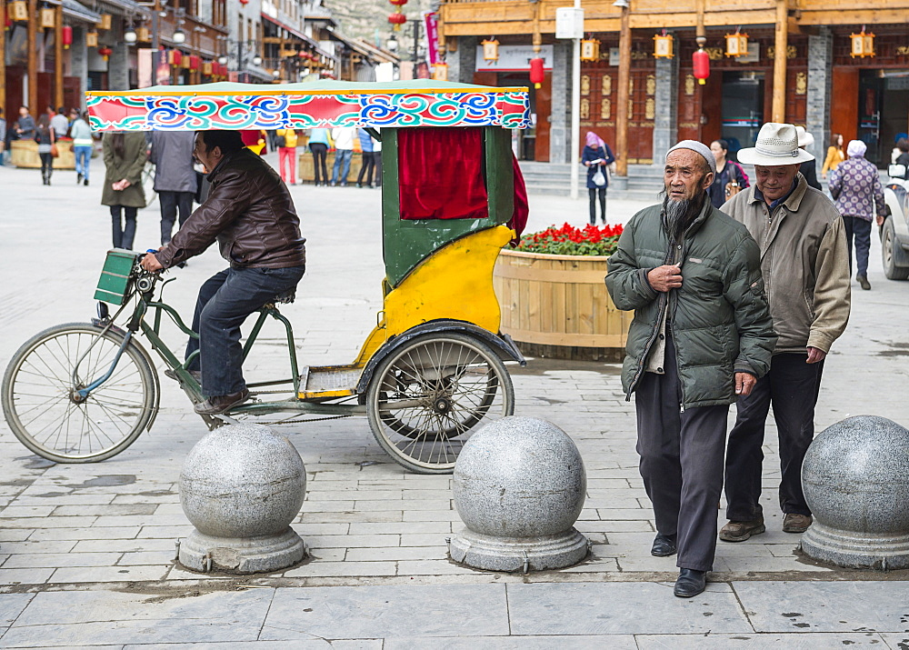 China, Sichuan, Songpan, Yawning trishaw driver and walking aged citizens.