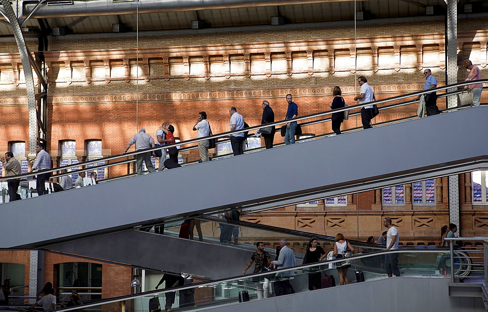 Spain, Madrid, Passengers using the escalators inside the terminus of the Atocha Railway Station.