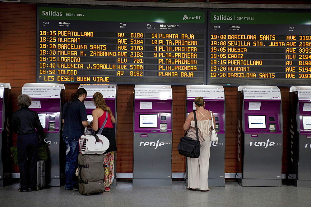 Spain, Madrid, Passengers using the self-service ticket machines in front of the departures board inside the terminus of the Atocha Railway Station