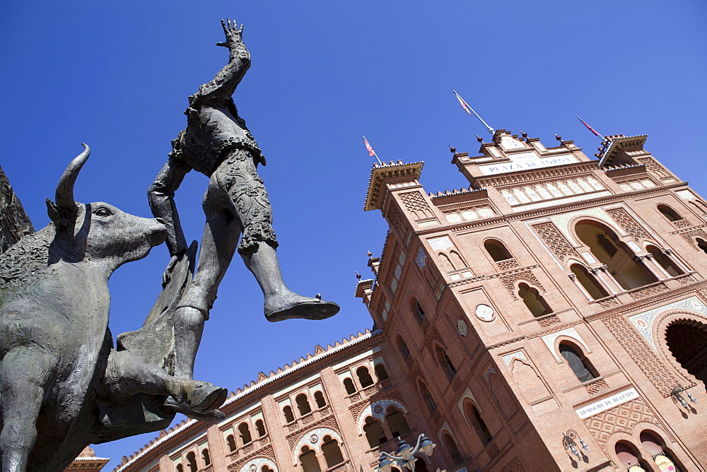Spain, Madrid, Statue of a matador with the Plaza de Toros de las Ventas in the background.
