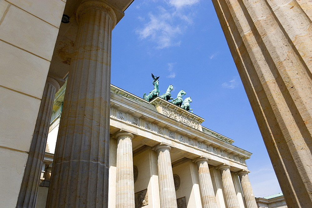 Germany, Berlin, Mitte, Brandenburg Gate or Brandenburger Tor seen between columns in Pariser Platz leading to Unter den Linden and the Royal Palaces with the Quadriga of Victory on top. The only remaining of the original 18 gates in the Berlin Customs Wall.