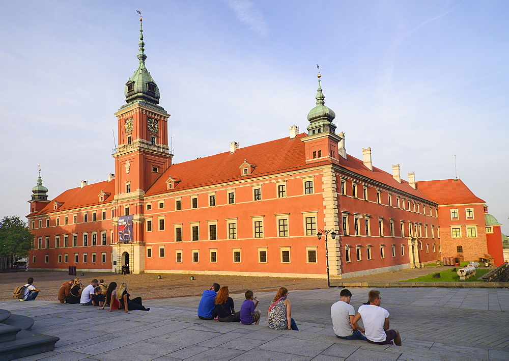 Poland, Warsaw, Royal Castle in Plac Zamkowy or Castle Square with people enjoying the evening sun.