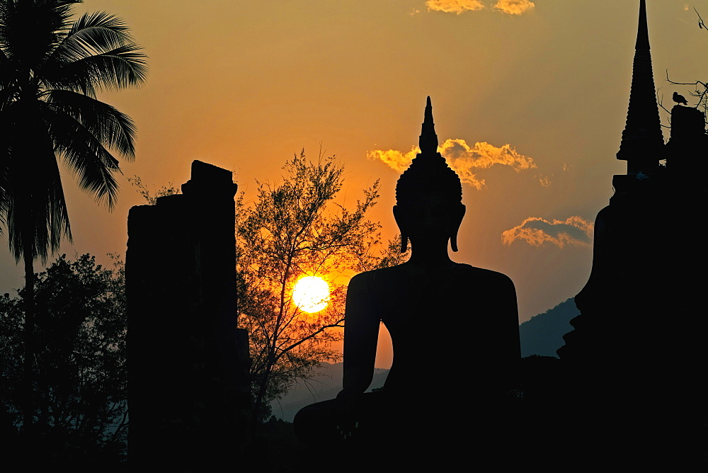 Thailand, Sukothai, Seated Buddha and stupa silhouetted against the setting sun, Wat Mahathat Royal Temple. - 797-12858