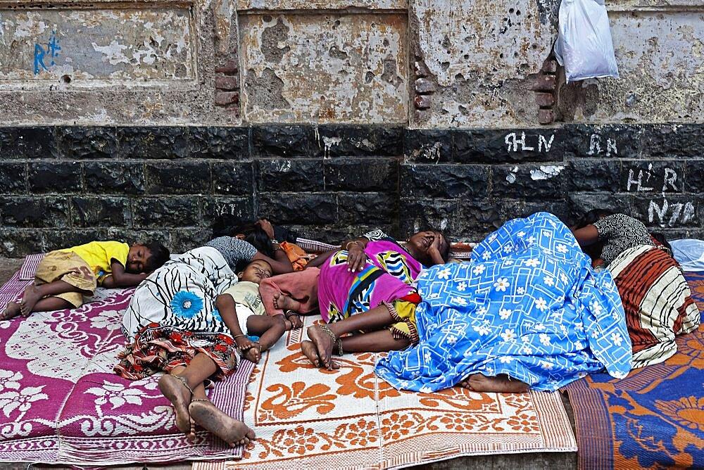 India, Maharashtra, Mumbai, Homeless family asleep on a pavement in central Bombay.