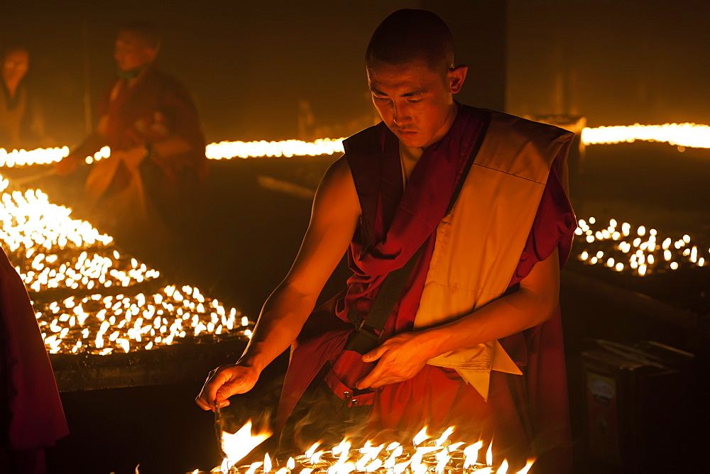 India, Bihar, Bodhgaya, Buddhist monk lighting merit-making candles in the grounds of the Mahabodhi Temple.