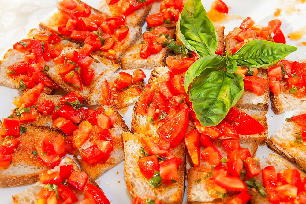 Italy, Tuscany, Lucca, Barga, Small slices of bread topped with tomato on display for a buffet. - 797-12888
