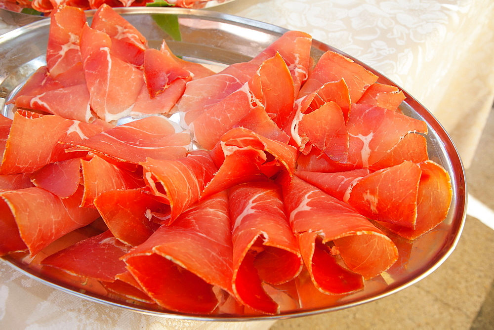 Italy, Tuscany, Lucca, Barga, Display of sliced meat as part of a buffet to be eaten with aperitifs.