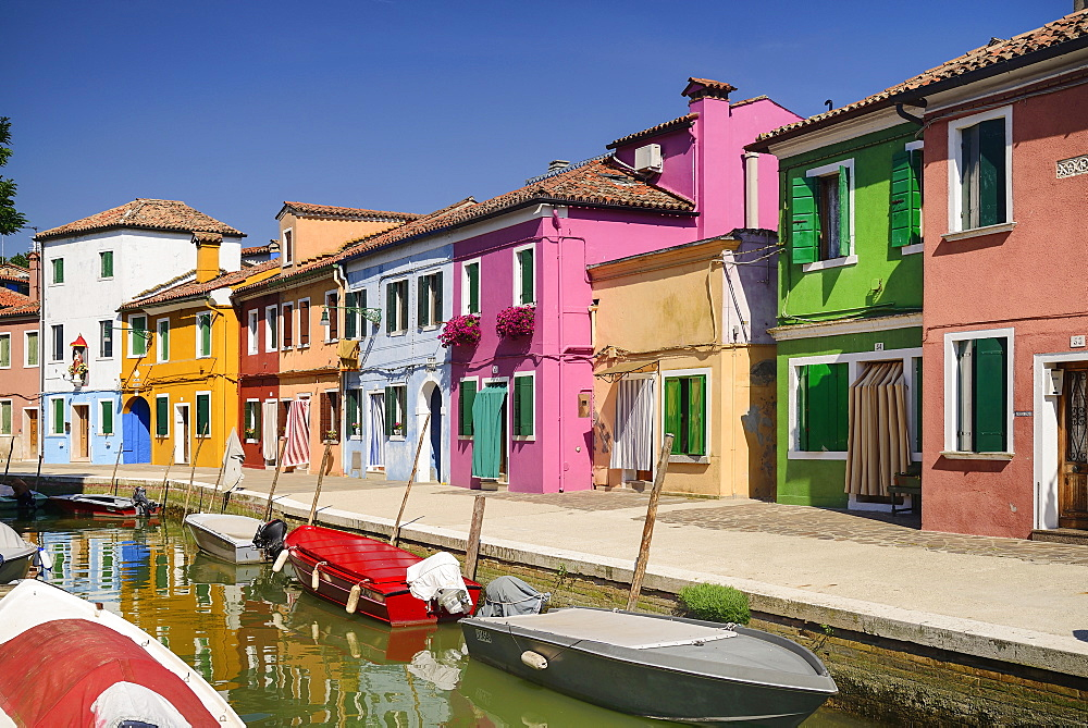 Italy, Veneto, Burano Island, Colourful row of house facades with boats on a small canal in the foreground.