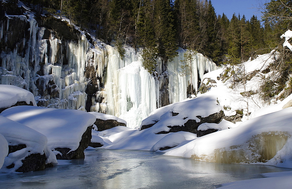 Norway, Golsjuvet, Frozen waterfalls with frozen river in foreground at climbing area close to Gol.