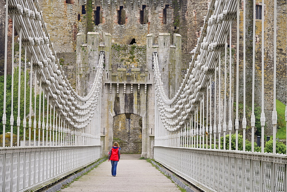 Wales, Conwy, Conwy Suspension Bridge with figure walking towards the walls of Conwy Castle.