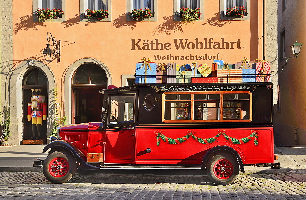 Germany, Bavaria, Rothenburg ob der Tauber, Kathe Wohlfahrt Christmas shop with present laden truck outside.