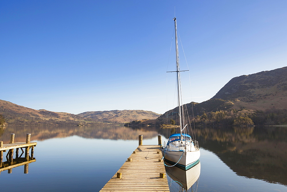 England, Cumbria, Lake District, Glenridding, Yacht moored at a jetty on Lake Ullswater.