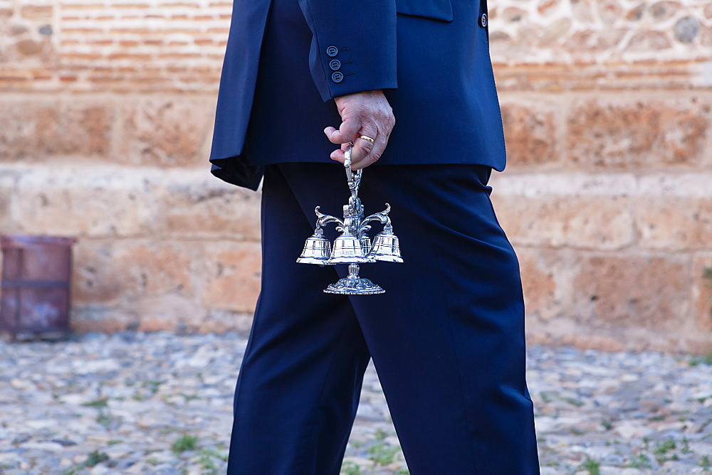 Spain, Andalucia, Granada, A man holds the cluster of small bells that are rung during the Corpus Christi procession.