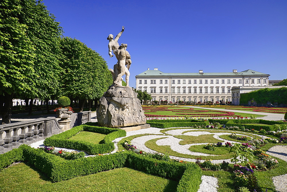 Austria, Salzburg, Mirabell Palace and Gardens with statue and flowerbeds in the foreground.