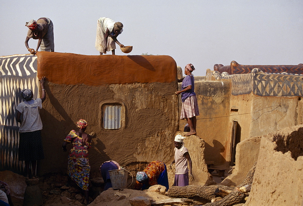 BURKINA FASO  Tiebele Group of women preparing house front for decorative painting in traditional Gourounsi village.