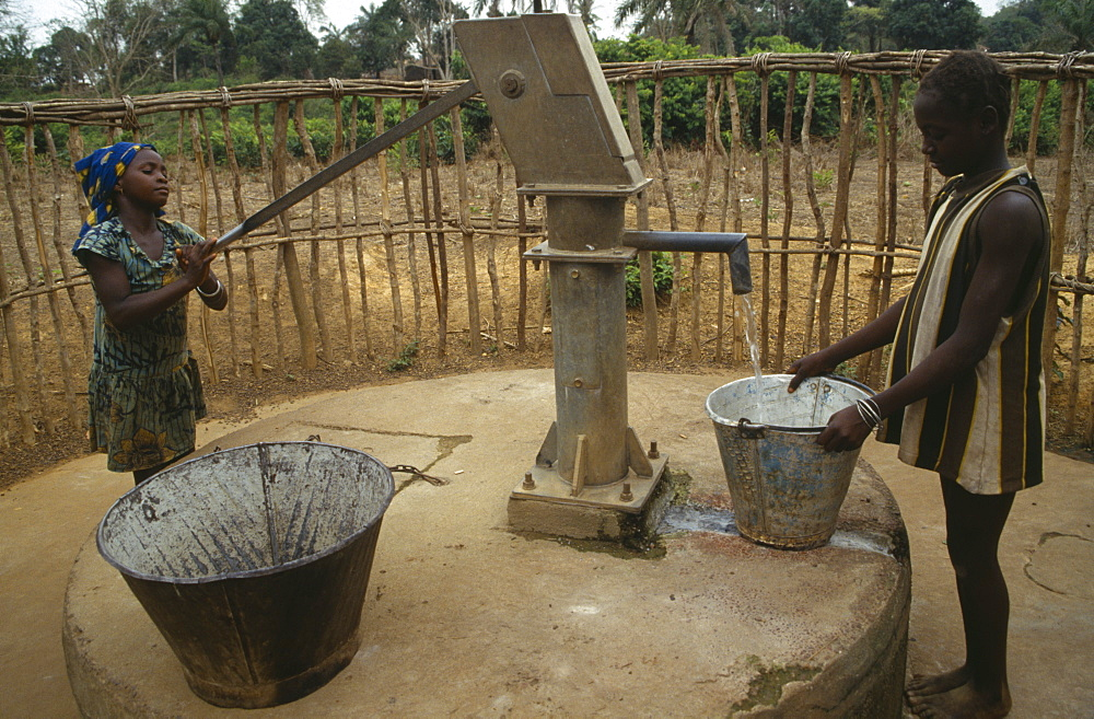 SIERRA LEONE  Kambia Young women using hand water pump.