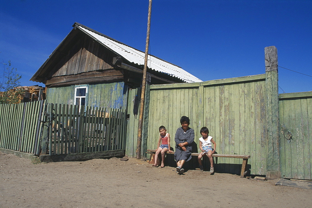 RUSSIA Lake Baikal Buryat woman and children outside painted wooden fence of house.  The Buryat are of Mongolian descent and are the largest ethnic minority group in Siberia.