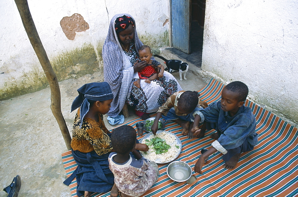 SOMALIA  Baidoa Woman and children eating lunch from communal dish using the right hand.  At a family meal men are usually served first and women and children eat seperately later.    - 797-2196