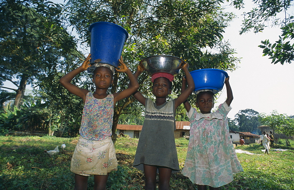 LIBERIA    Nimba Saclepea Three children carrying water vessels on their heads.