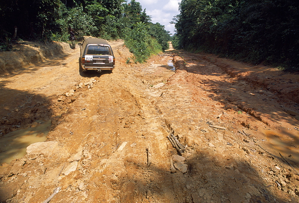 LIBERIA    Nimba Zinakopa Car on unmade road with deep ruts through mud in foreground.    Automobile   Automobile