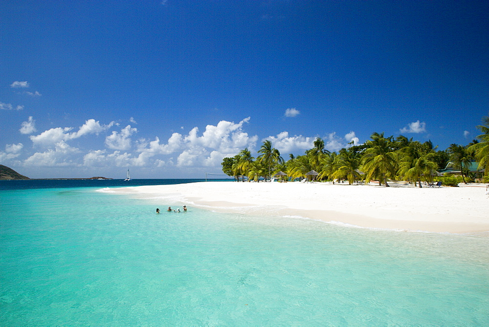 WEST INDIES St Vincent & The Grenadines Palm Island The beach at Palm Island Resort with guests sitting in the water