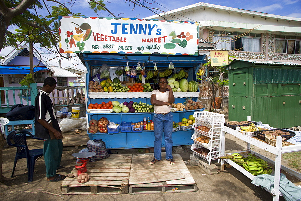 WEST INDIES St Vincent & The Grenadines Union Island Fruit and vegetable market stall with owner in Hugh Mulzac Square in Clifton