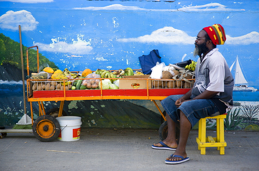 WEST INDIES St Vincent & The Grenadines Union Island Fruit and vegetable stall holder in front of wall painting in Clifton