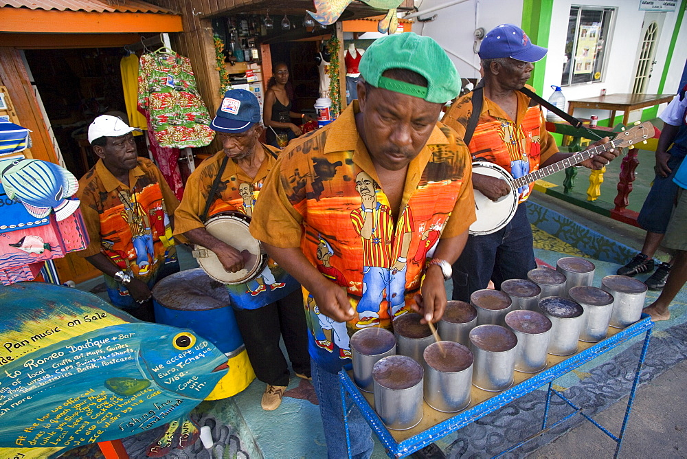 WEST INDIES St Vincent & The Grenadines Union Island Miniature steel drum pan player and band playing at a roadside bar during Easterval Easter Carnival in Clifton          - 797-2403