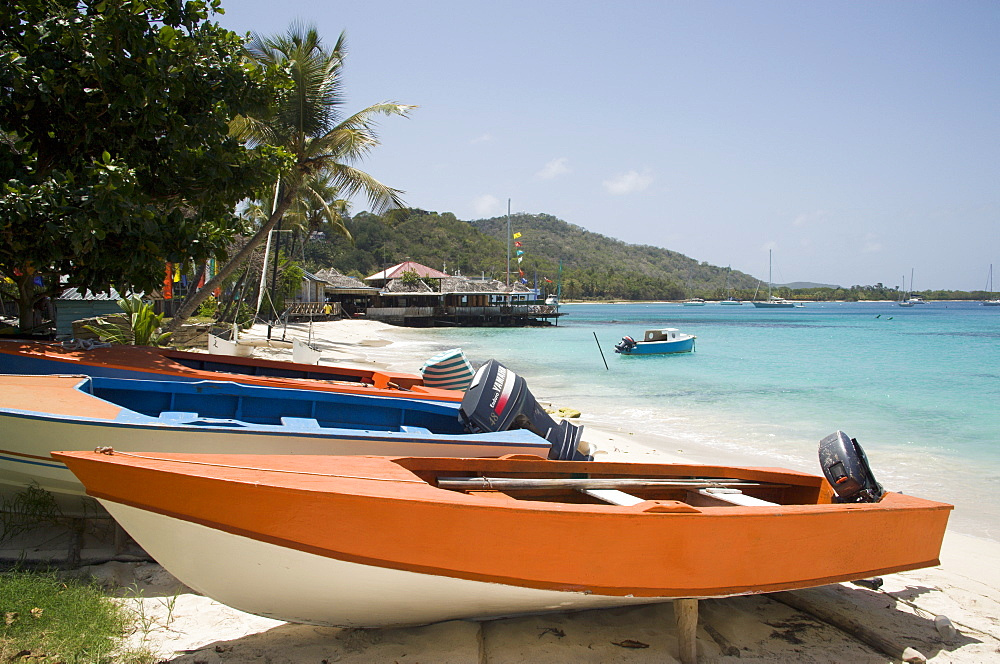 WEST INDIES St Vincent & The Grenadines Mustique Fishing boats on beach in Britannia Bay with Basils Bar beyond