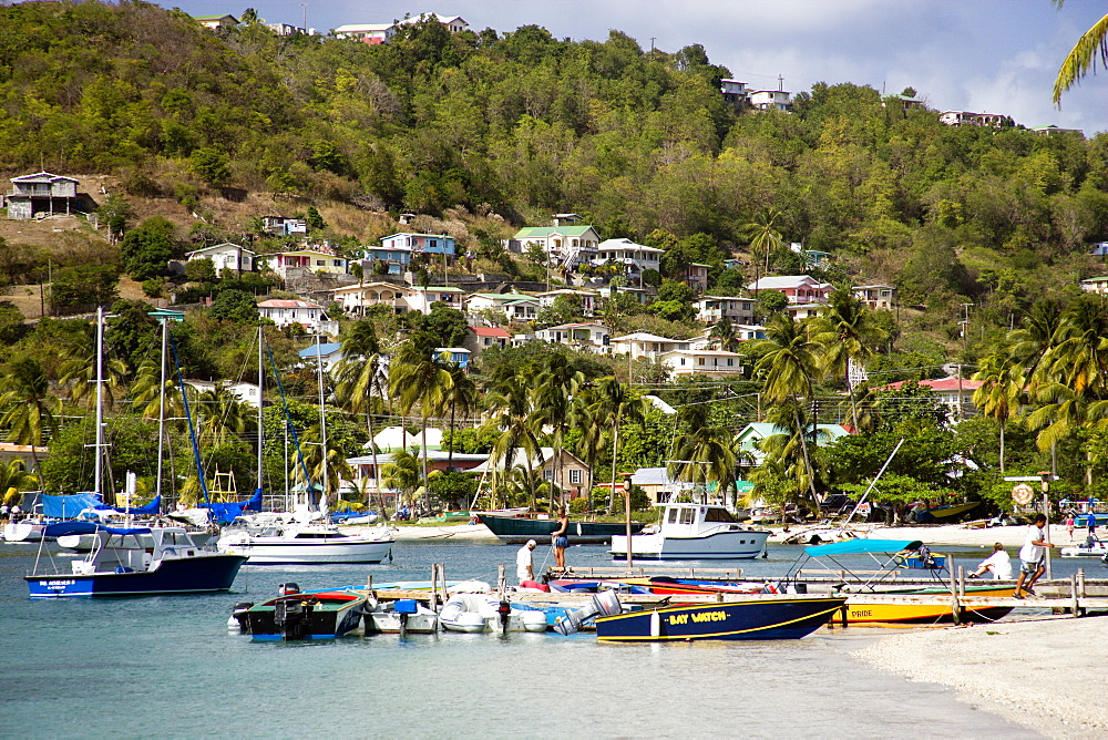 WEST INDIES St Vincent & The Grenadines Bequia Jetty with moored yachts in Admiralty Bay with hillside houses beyond in Port Elizabeth