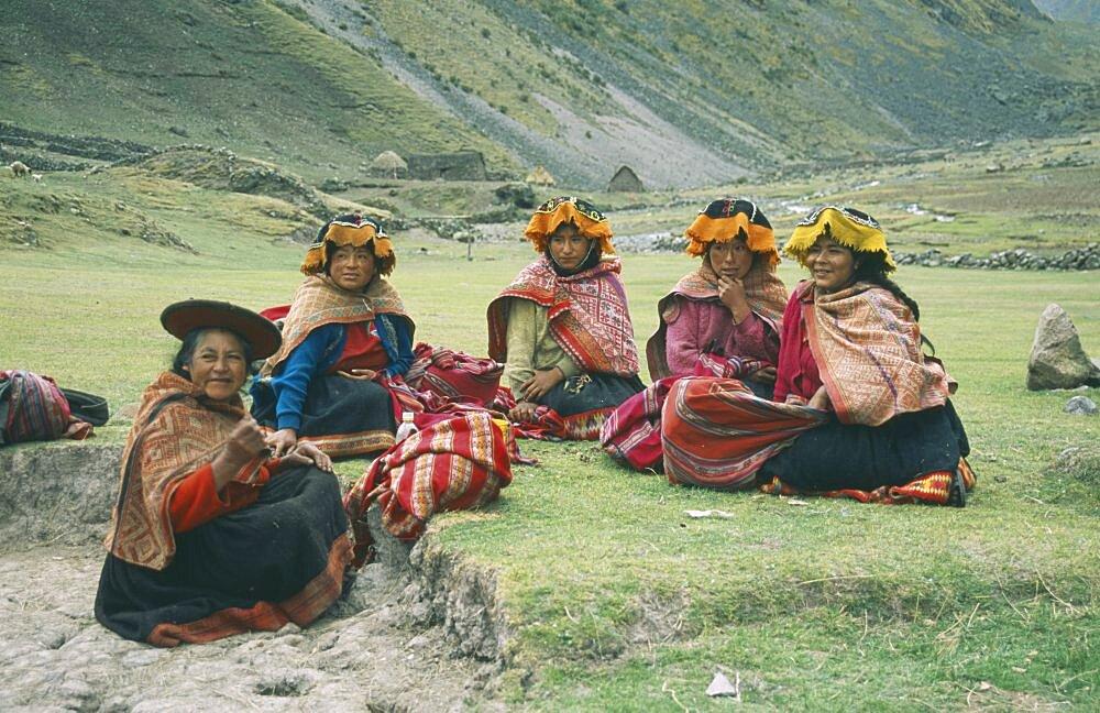 PERU Cusco Cancha Cancha Local Quechuan women sat on grass  wearing traditional dress.  Cuzco  Sacred Valley  Andes  Cuzco  Sacred Valley  Andes