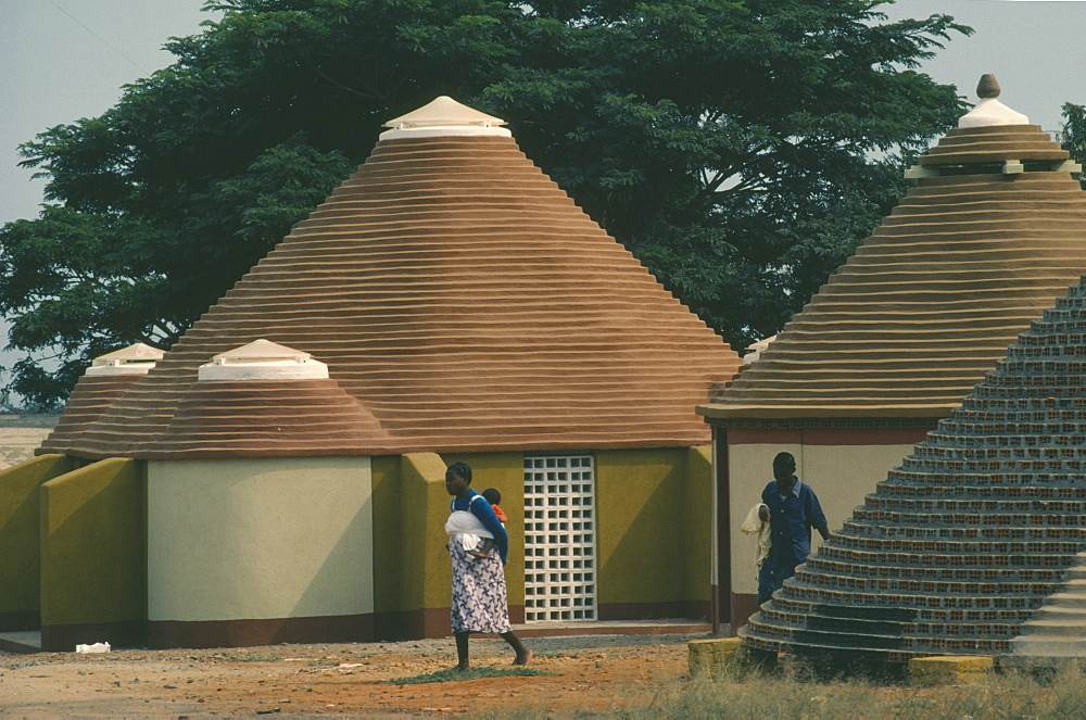 ANGOLA  Tradtional Homes Women and child outside new village housing.