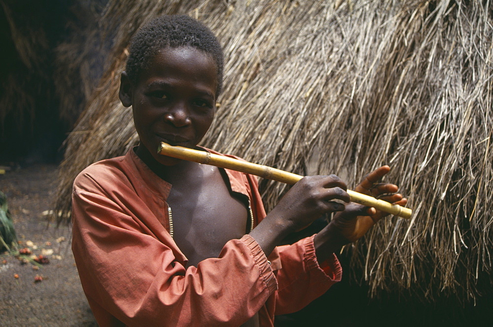 SIERRA LEONE  Kambia Young boy playing home made flute.