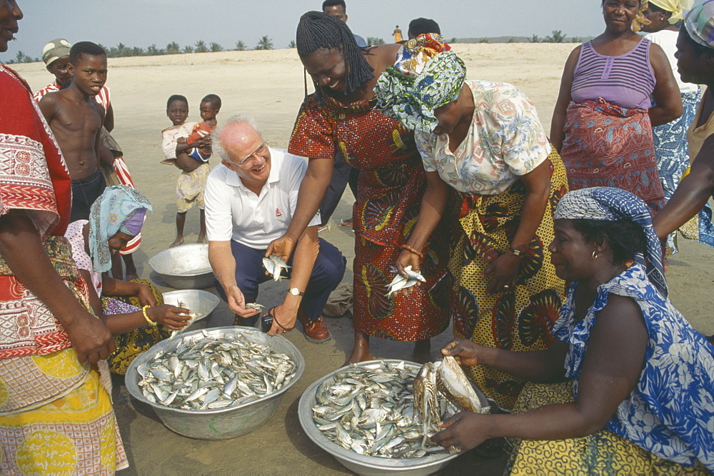 GHANA  People Western man talking to women selling fish on beach near Accra.