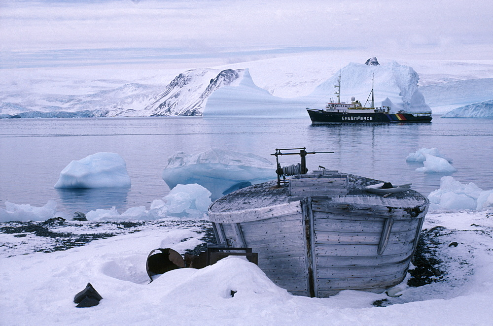 ANTARCTICA  King George Island Old whale boat on land with Greenpeace ship in distance.