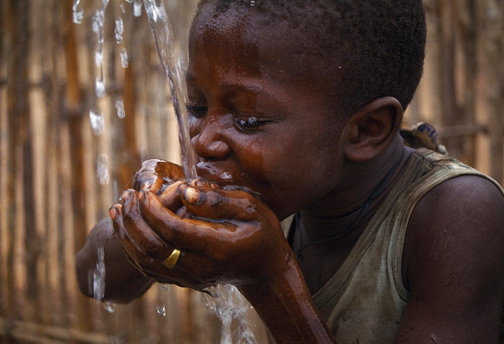 SIERRA LEONE  Water Child cupping his hands together drinking well water African Kids Western Africa Children