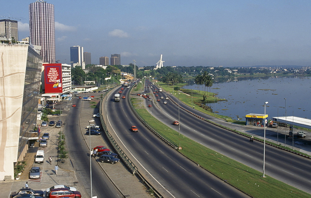 IVORY COAST  Abidjan Cityscape with multi lane traffic  skyscrapers and distant view towards modern exterior of St Paul s Cathedral. Côte d Ivoire Cathédrale St-Paul